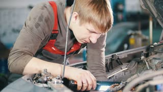 Mechanic with lamp checks and repairs automotive engine, car repair, working in the workshop, work under the hood