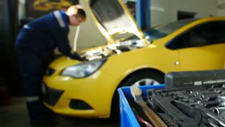 Mechanic works in professional auto service near repairs yellow car, time-lapse