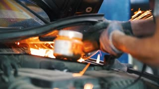Mechanic's hands welds a part of the car with a welding machine