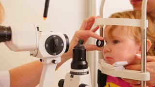Medical concept - child's ophthalmology - doctor optometrist checks eyesight at little girl