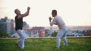 Men with a strong physique show Brazilian dance capoeira, fun fighting on the grass, smiling