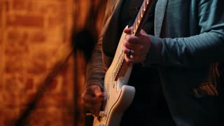 Men's hands playing bass for a performance in a jazz bar