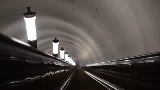 Metro. Ride the escalator past the lamps. Railings. Dim lights.