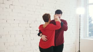Middle age female and young man in red shirt is dancing kizomba in studio