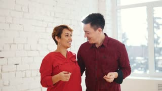 Middle age woman and young man is dancing kizomba in studio, close up