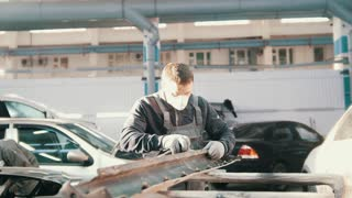 Midle age caucasian man - worker doing manual labour in automobile service - repairing the car