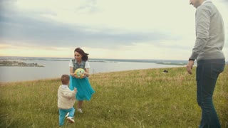 Mom plays with a small child in the ball, the child runs to her, the ball flies to dad, overcast, summer day