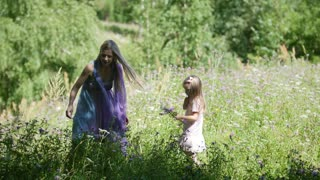 Mother and her little daughter collects the flowers at meadow