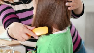 Mother hands is combing hair to her little daughter