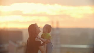 Mother playing with little child at sunset - throws the son