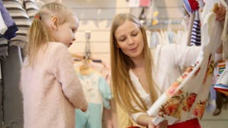 Mother with blonde daughter buying dress - kids clothes in store