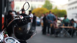 Motorcycle helmet hanging on the handles of the motorcycle hazy background with people