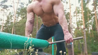 Muscular body-builder exercising with huge heavy iron equipment outdoors in forest