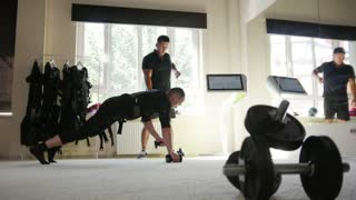 Muscular fitness instructor works with athlete wearing ems suit