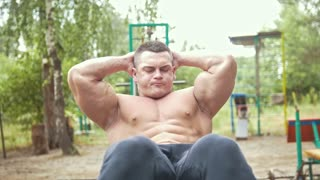 Muscular man doing exercises for abs muscles at the sports park outdoors