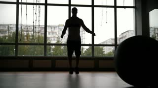 Muscular man doing rope jump work-out in the gym - silhouette, slow-motion