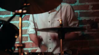 Musician in a white shirt playing drums for a performance in a jazz bar