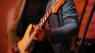 Musician plays guitar at a concert in a jazz bar