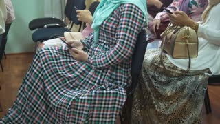 Muslim women in long dresses at the islamic conference uses a smartphones