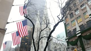 NEW YORK, USA - DECEMBER, 2017: Cathedral and skyscrapers in fog, view from bottom, american flags on the building