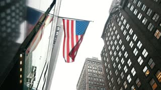 NEW YORK, USA - DECEMBER, 2017: Skyscrapers in fog, view from bottom, american flag on the building