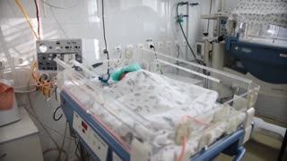 Newborn premature baby sleeping in bed in the maternity hospital