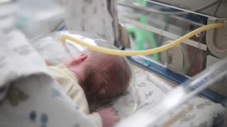 Newborn premature baby with artificial respiration apparatus sleeping in bed in the maternity hospital