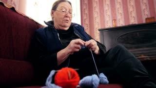 Old lady home at sofa knits wool socks