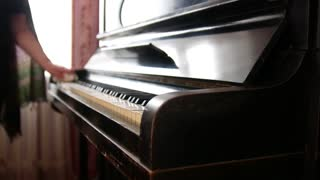 Old woman at home wipes the dust on piano - close up