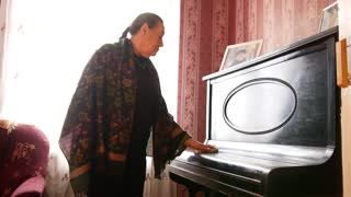 Old woman at home wipes the dust on piano