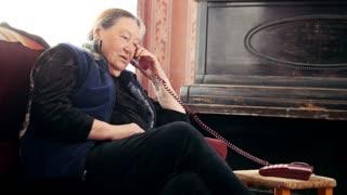 Old Woman pensioner speaks phone, telephoto