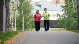 Old women walking on sidewalk in an autumn park during a scandinavian walk