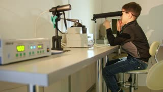 Ophthalmology clinic - child checks eyes vision with high technology device