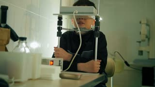 Ophthalmology clinic - child teenager checks eyes vision with high technology device