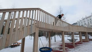 Parkour - a free runner blonde male jumps at winter snow park, slow motion