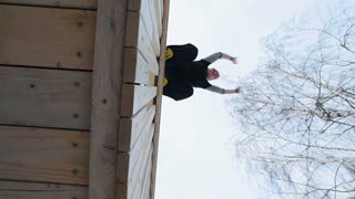 Parkour - a free runner blonde man jumps a flip at winter snow park, slow motion