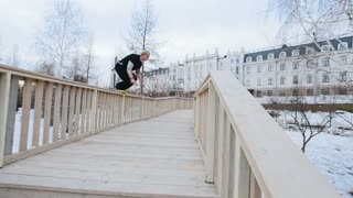 Parkour - a free runner blonde man jumps at winter snow park, slow motion