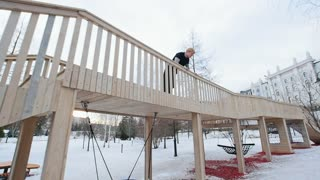 Parkour - a free runner jumps at winter snow park, slow motion