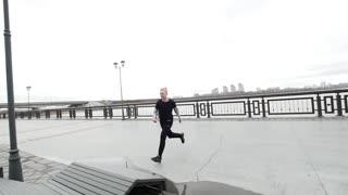 Parkour - a tracer blonde man jumps a flip outdoor