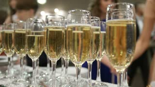 People drinks champagne on event - glasses with alcohol on table