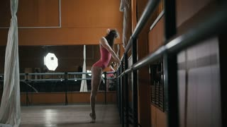 Petite girls-gymnasts on ballet bar, slow-motion