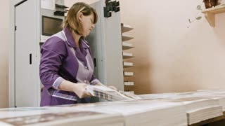 Polygraph industry - woman working on folder machine in printing house