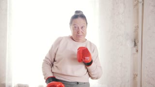 Portrait o old senior woman boxing in front of window
