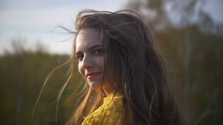 Portrait of beautiful young woman with red lips and yellow jacket at sunset