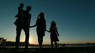 Portrait of full family - Father, mother, daughter and little son - silhouette at sunset, in front of skyline