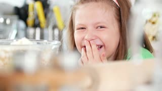 Portrait of funny little girl laughing at cooking studio