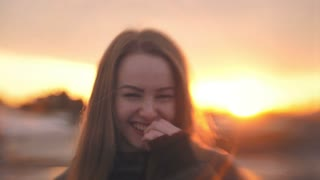 Portrait of happy young woman smiling at sunset