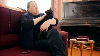 Portrait of old lady at home - old lady sits on sofa with black cat - close up