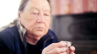 Portrait of senior lady - elderly woman at home takes the pills medication packages - pension healthcare