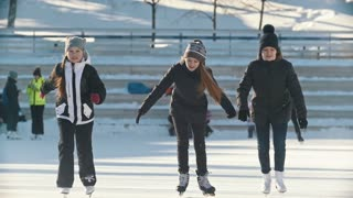 Portrait of three teenage girls wearing winter clothes at the rink